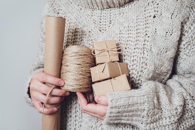 Presentes, papel artesanal, um rolo de corda nas mãos de mulheres, close-up. conceito de presentes artesanais. tendência moderna, embalagem natural para presente. fundo de férias.