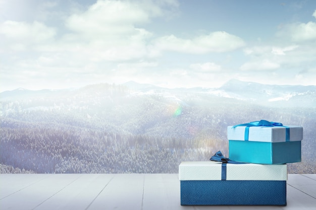 Presentes para a família ou amigos e a paisagem das montanhas no fundo. caixas e perfumes na frente de montanhas nevadas e céu nublado. dia de inverno, feriados, viagens, época de ano novo e natal. .