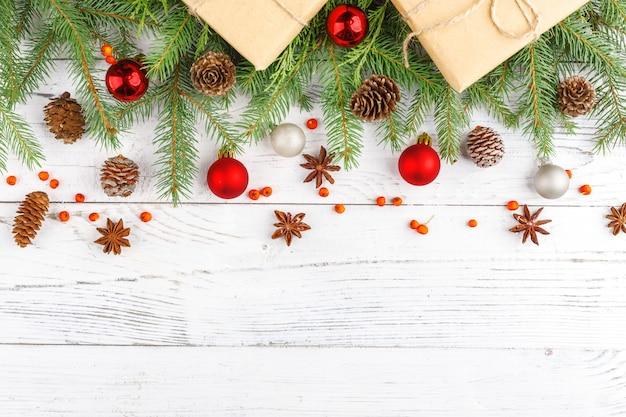 Presentes para o ano novo embrulhado em papel ofício perto de ramos de abeto e cones em fundo branco de madeira vista superior copyspace