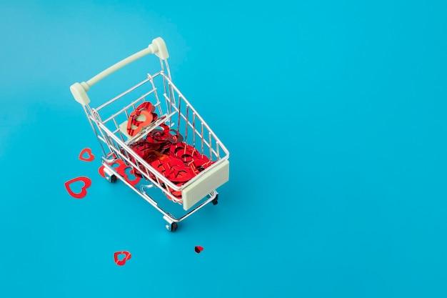 Presentes românticos para o dia dos namorados, muitos corações em uma cesta do supermercado em um fundo azul com espaço de cópia