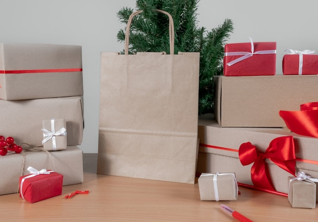 Presentes, sacola de compras, árvore de natal e caixas de embalagem em cima da mesa, conceito de entrega.