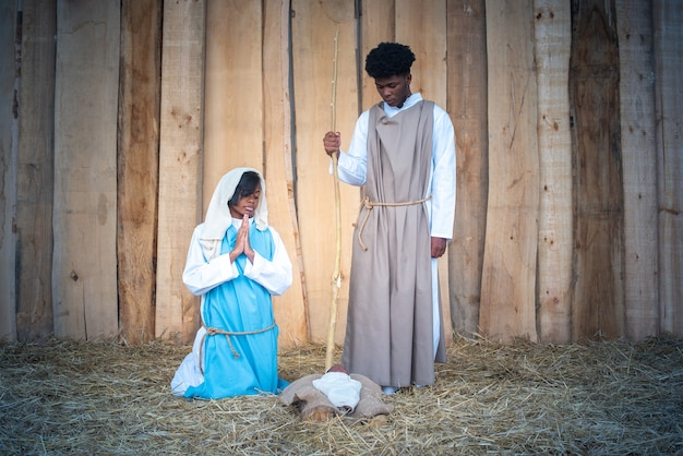 Presépio de um berço com a virgem maria e josé de etnia africana rezando e olhando o bebê jesus