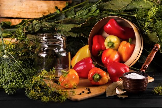 Preservação de vegetais. em cima da mesa estão pimentões, cebolas, alho, saleiro.