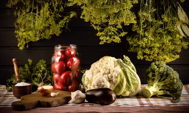 Preservação de vegetais. sobre a mesa está um pote de tomate, saleiro, alho, cebola, couve-flor, brócolis. cachos de endro pairam sobre eles.