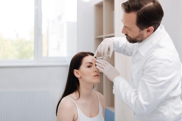 Preservando a beleza. mulher bonita e admirável querendo parecer mais jovem e pedindo a um profissional para fazer levantamento de peso com botox
