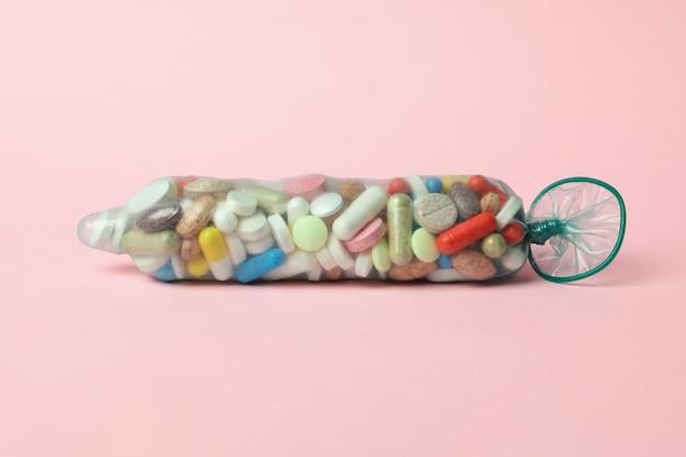 Preservativo cheio de comprimidos em fundo rosa