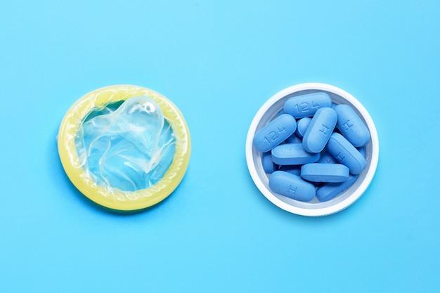 Preservativo com prep (profilaxia pré-exposição) usada para prevenir o hiv, na tampa do frasco de comprimidos de plástico sobre fundo azul. salvar sexo