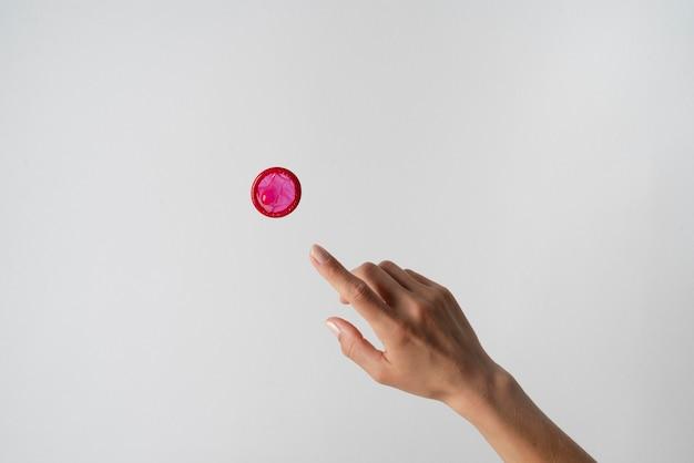 Preservativo de mão e vermelho fecham