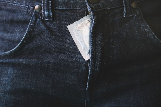 Preservativo dentro de uma calça. previna a infecção e os contraceptivos controlam a taxa de natalidade ou são profiláticos seguros.