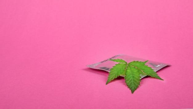 Preservativo e folha de cannabis no fundo rosa cópia espaço contracepção conceito de drogas sexuais