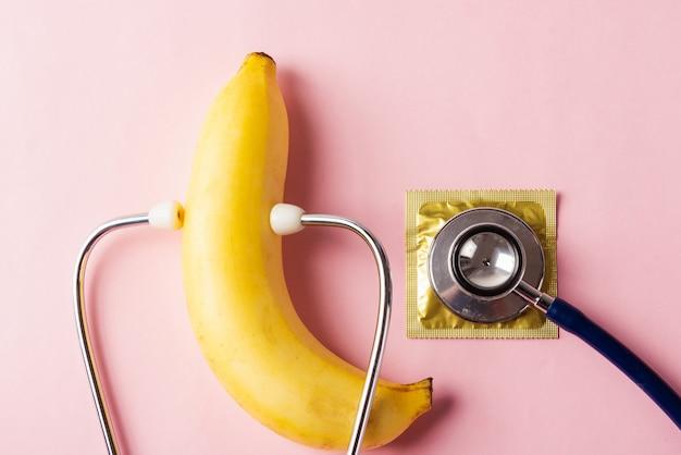 Preservativo em embalagem de embalagem, banana e estetoscópio médico