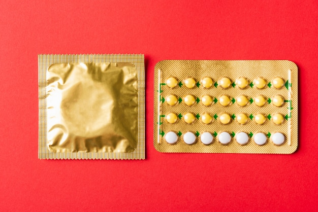 Preservativo na embalagem e pílulas anticoncepcionais com bolhas nas pílulas anticoncepcionais hormonais