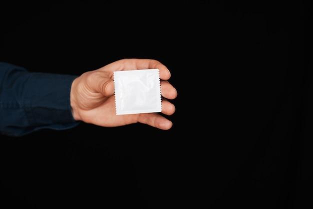 Preservativo na embalagem na mão do homem