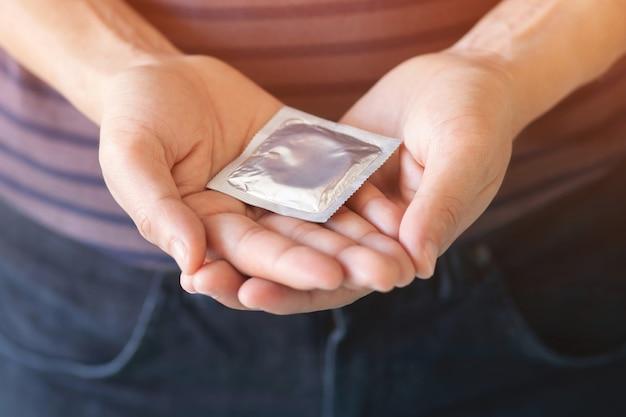 Preservativo na mão de um homem. previna a infecção e os contraceptivos controlam a taxa de natalidade ou são profiláticos seguros.