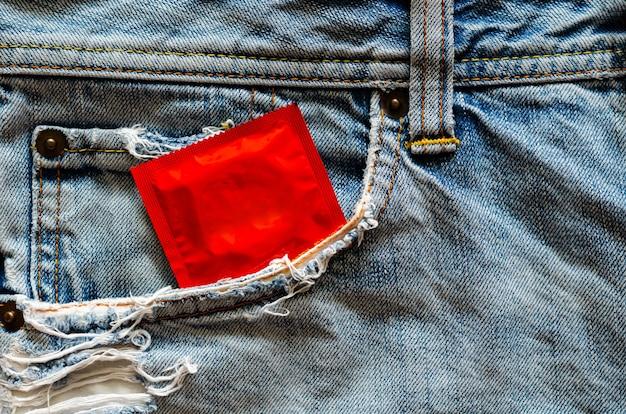 Preservativo no bolso da calça jeans para sexo seguro, saúde sexual mundial e conceito do dia da aids