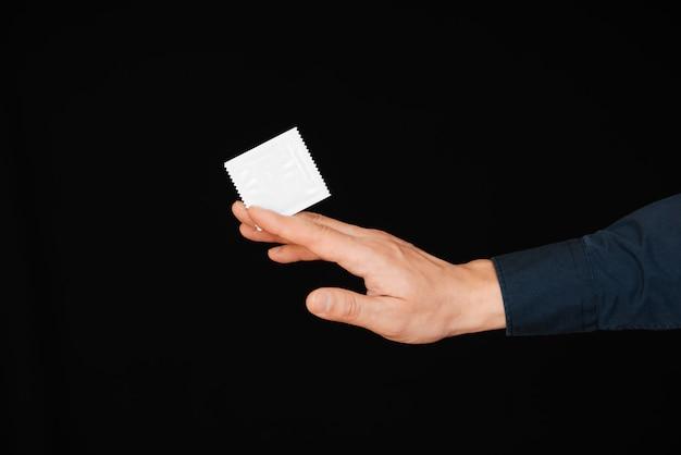Preservativo no pacote na mão do homem