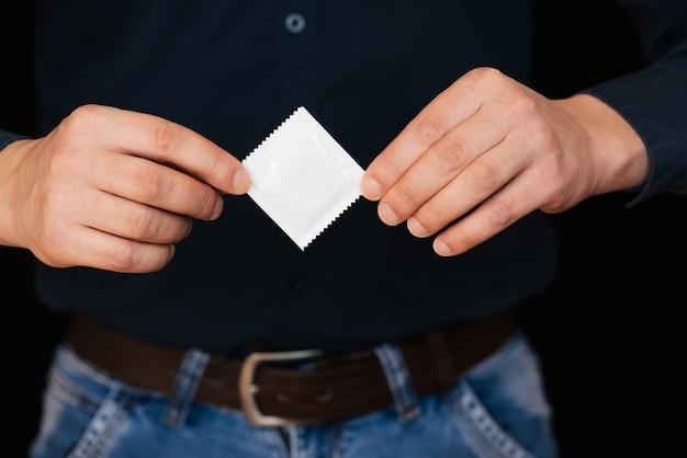 Preservativo para contracepção e proteção nas mãos masculinas