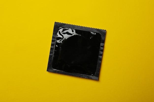 Preservativo preto em branco na superfície amarela