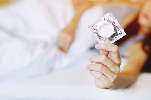 Preservativo pronto para usar nas mãos femininas, dar o conceito de sexo seguro do preservativo na cama.
