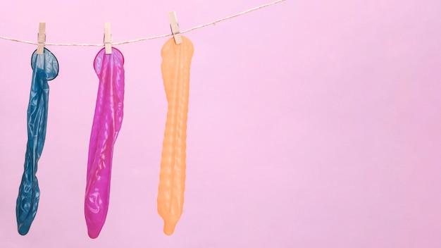 Preservativos coloridos com prendedor de roupa e cópia-espaço