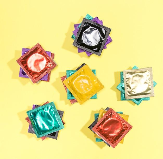 Preservativos coloridos da vista superior nos envoltórios