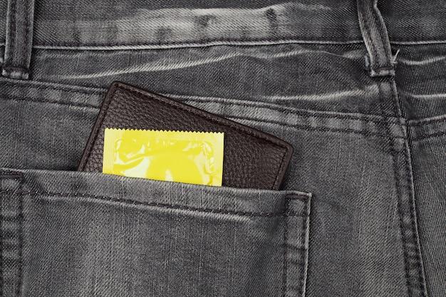 Preservativos e carteira no bolso da calça jeans cinza.