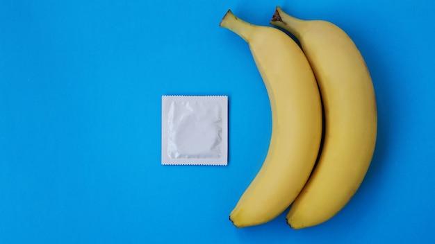 Preservativos e duas bananas juntas sobre fundo azul, o conceito de contraceptivos e a prevenção de doenças venéreas do casamento entre pessoas do mesmo sexo.
