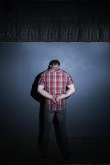 Preso criminoso masculino em fundo de arame farpado. detido homem irreconhecível com as mãos atrás das costas, pessoa punida à noite, conceito culpado