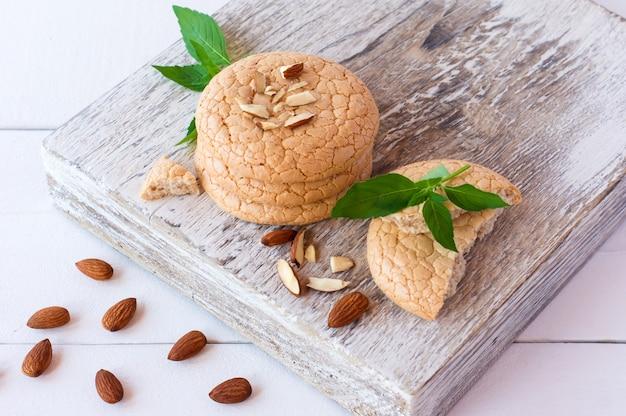 Preso de biscoitos de amêndoa com menta e nozes na tábua de corte branca.