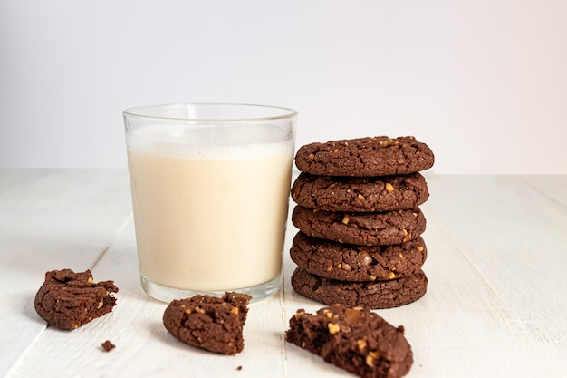 Preso de biscoitos de brownie de chocolate e copo de leite de coco no fundo de madeira. pastelaria caseira