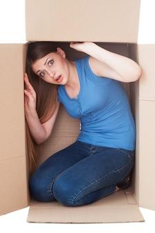 Preso dentro. jovem chocada olhando para a câmera sentada em uma caixa de papelão