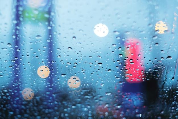 Preso no trânsito em dia chuvoso, gotículas no pára-brisa com fundo embaçado e bokeh