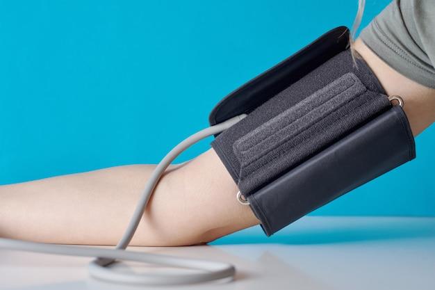 Pressão sanguínea de medição da mulher com o monitor digital da pressão contra a parede azul. cuidados de saúde e conceito médico