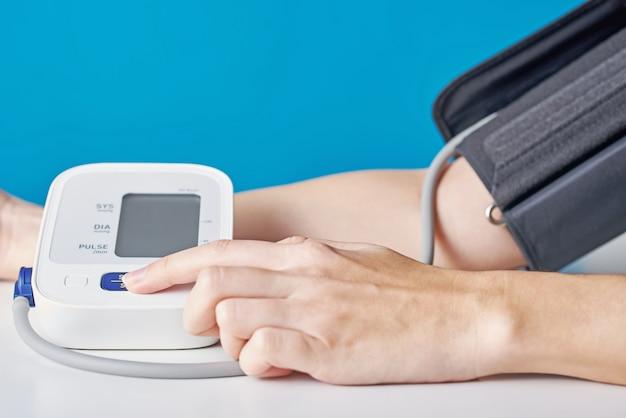 Pressão sanguínea de medição da mulher com o monitor digital da pressão contra o azul. cuidados de saúde e conceito médico
