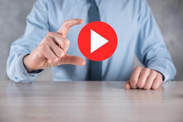 Pressionando empresário, segure o sinal de botão de reprodução para iniciar ou iniciar projetos. apresentação de reprodução de vídeo. ideia para negócios, botão do player technology.media. ícone de jogo.