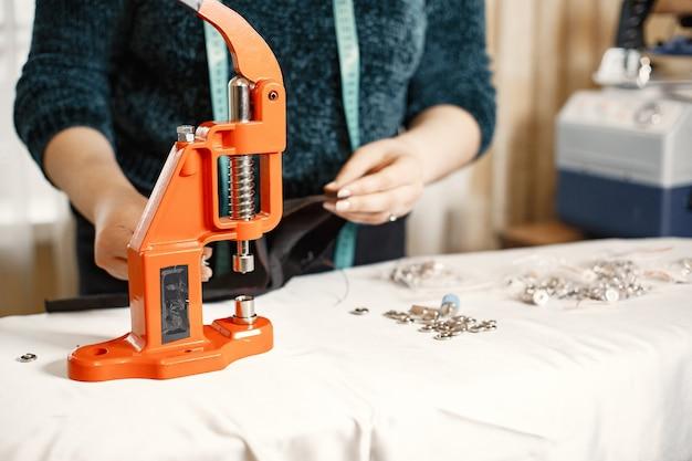 Pressione laranja para roupas. botões em tecido. mulher com ferramentas de costura