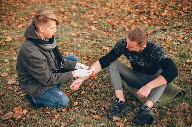 Prestando primeiros socorros no parque. braço ferido enfaixado de homem. guy ajuda um amigo.
