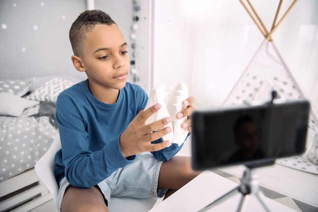 Preste atenção. garoto blogueiro afro-americano pensativo estudando modelo de mandíbula enquanto grava um vídeo