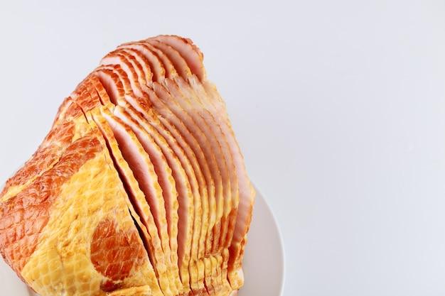 Presunto de porco defumado de nogueira fatiada em espiral inteira isolado no fundo branco.