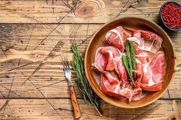 Presunto de porco jamon serrano em fatias espanholas. fundo de madeira. vista do topo. copie o espaço.