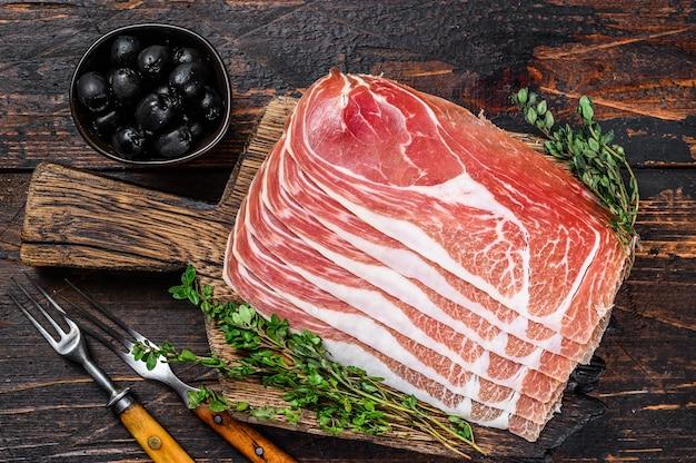 Presunto jamon serrano tradicional espanhol fatiado em uma placa de corte. fundo de madeira escuro. vista do topo.
