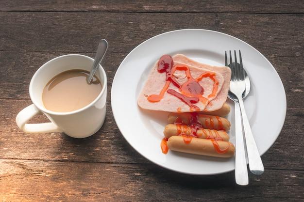 Presunto, salsicha e café em um fundo de madeira