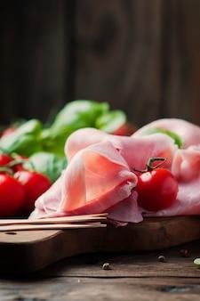 Presunto tradicional italiano com tomate e manjericão na mesa de madeira