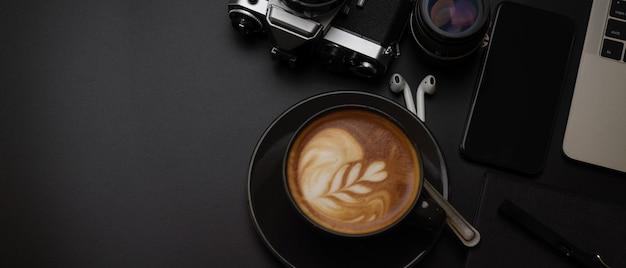 Preta xícara de café na mesa de escritório escura com laptop, câmera, suprimentos e cópia espaço