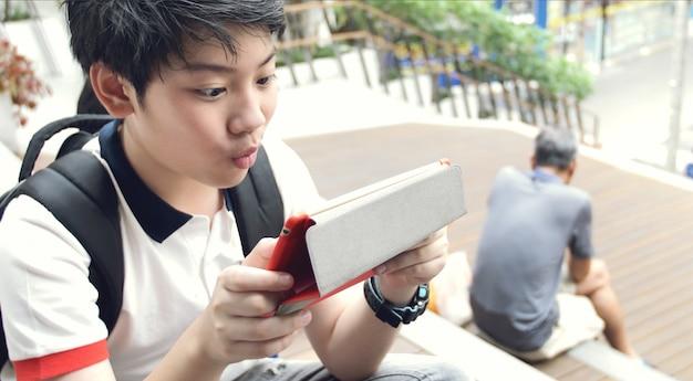 Preteens asiáticos que olham no tablet pc, cara do sorriso.
