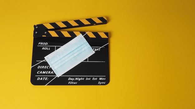 Preto com claquete amarelo ou ardósia de filme com máscara facial. é usado na produção de vídeo e na indústria do cinema em fundo amarelo.