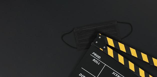 Preto com claquete amarelo ou ardósia de filme e máscara facial preta em fundo preto preto.