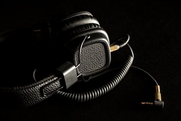 Preto com fio em fones de ouvido com fone de ouvido de ouro sobre fundo escuro.