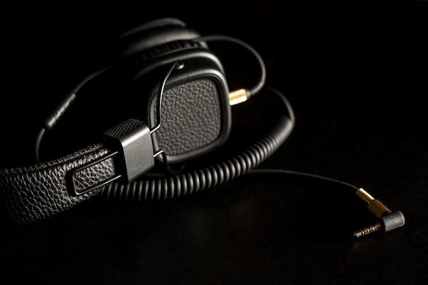 Preto com fio nos fones de ouvido com fone de ouvido dourado no escuro
