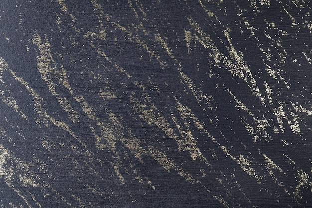 Preto com lantejoulas cintilantes douradas. superfície escura espalhada com cristais de ouro